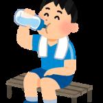 運動後に休憩して水を飲んでいる少年