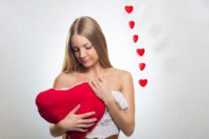 ハート型のクッションを抱きしめる女性