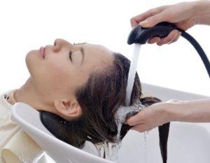 シャンプー台で髪を洗ってもらっている人
