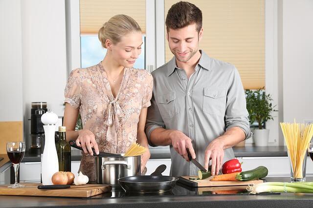 キッチンで料理をしているカップルの写真
